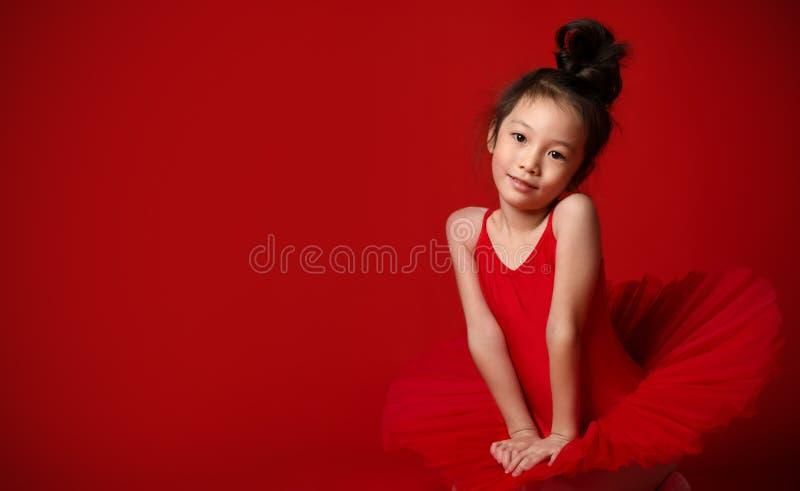 美丽的礼服的逗人喜爱的女孩芭蕾舞女演员在红色跳舞 免版税图库摄影
