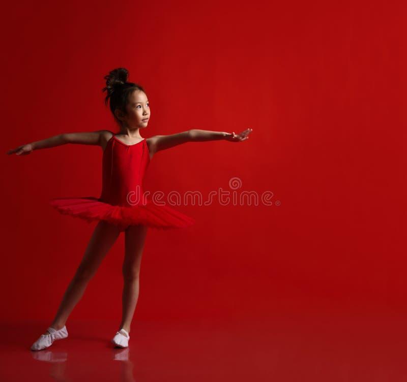 美丽的礼服的逗人喜爱的女孩芭蕾舞女演员在红色跳舞 图库摄影