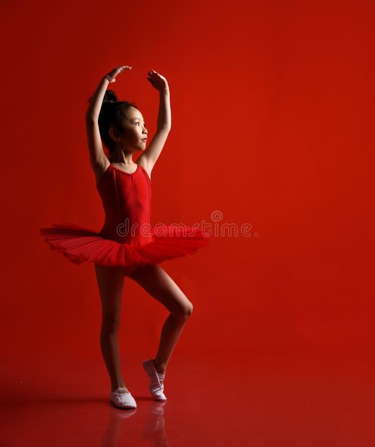 美丽的礼服的逗人喜爱的女孩芭蕾舞女演员在红色跳舞 库存照片