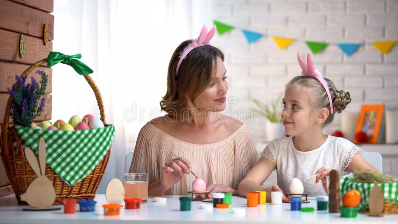 美丽的看彼此,绘的复活节彩蛋,感觉的爱的妈妈和女孩 库存图片
