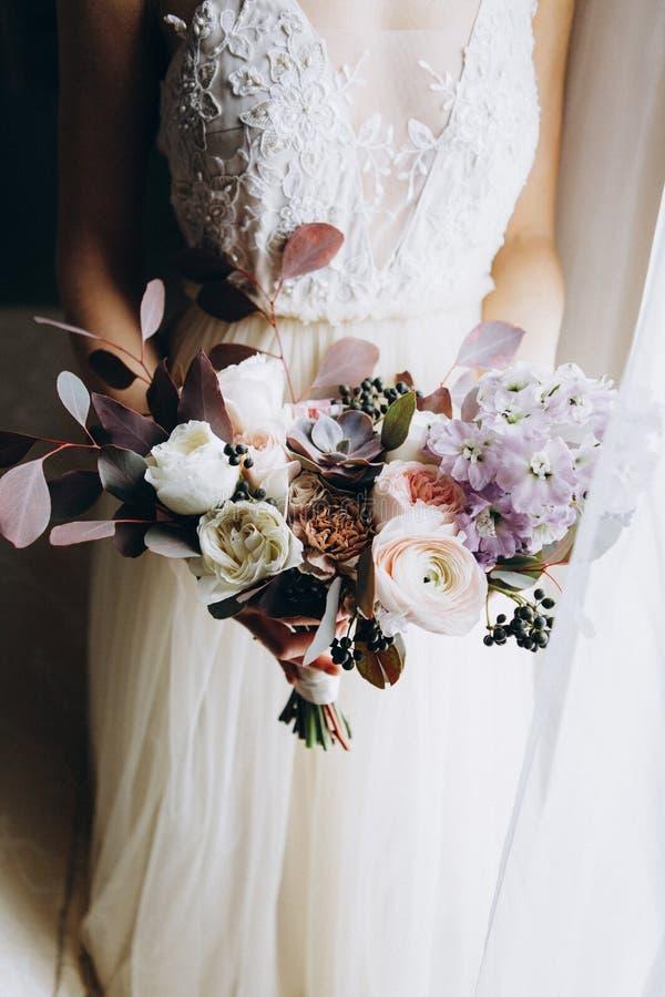 美丽的现代桃红色和白色花束在新娘的手上 关闭用不同的花的婚姻的花束 库存图片
