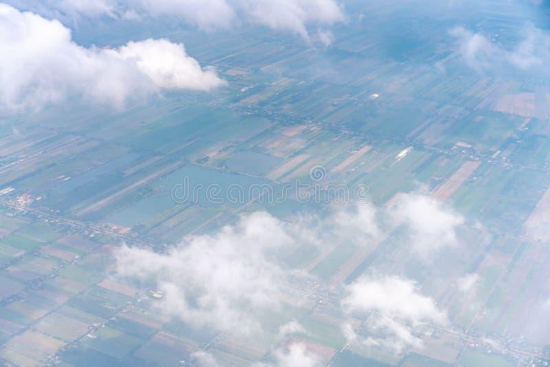 美丽的白色云彩在领域视图上的天空蔚蓝漂浮从飞机 免版税库存照片