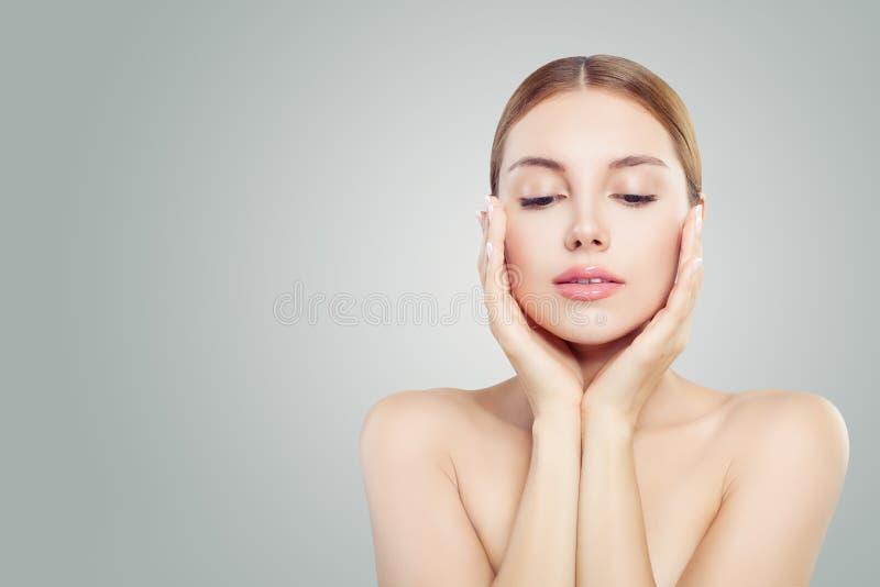 美丽的表面 俏丽的妇女在她的手上的握她的面孔 面部治疗,整形的,防皱和皮肤护理概念 库存图片
