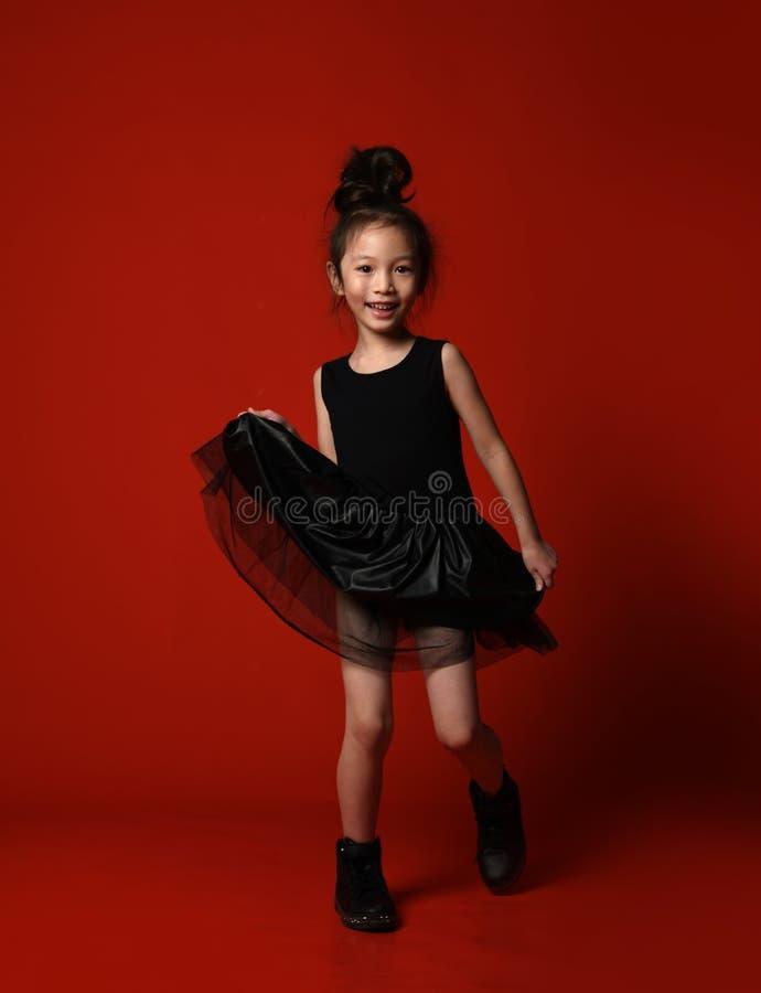 美丽的黑礼服的逗人喜爱的矮小的亚裔女孩芭蕾舞女演员跳舞愉快微笑在红色充分的身体 库存图片