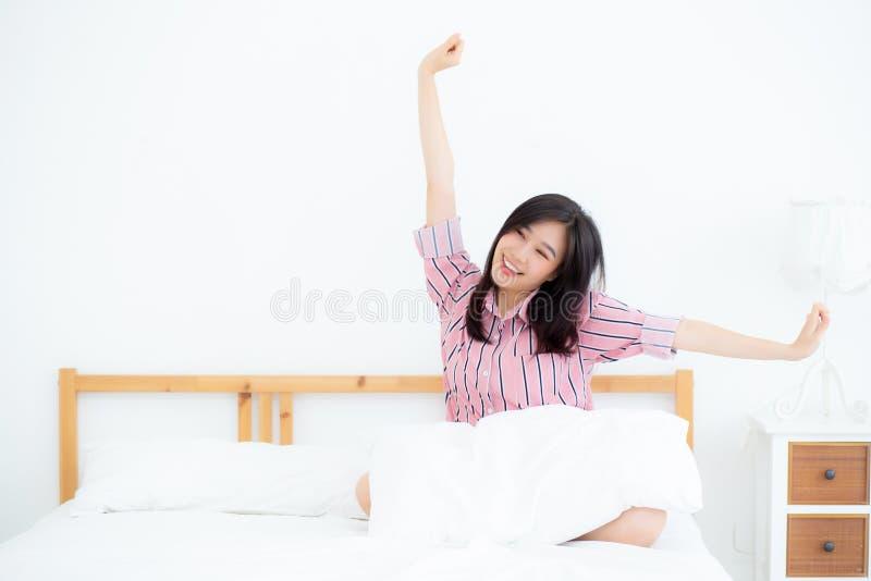 美丽画象年轻亚洲妇女舒展和放松在床上以后在卧室叫醒早晨 免版税库存照片