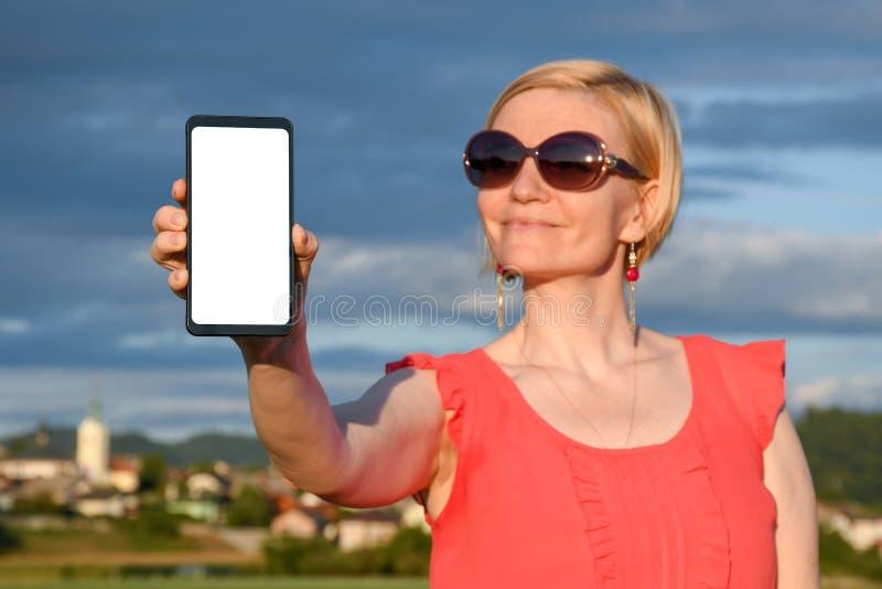美女佩带的太阳镜,当在手中拿着智能手机时 免版税库存图片