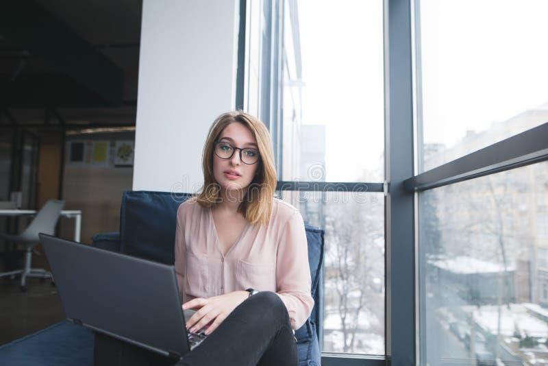 美女坐与膝上型计算机在沙发在办公室和神色在照相机 工作在一个现代办公室 免版税库存图片