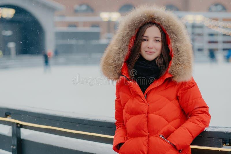 美女水平的射击红色外套的,在溜冰场保留在口袋的手,享受时间,来,呼吸新鲜空气 库存图片