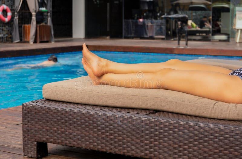 美女腿在游泳场附近晒日光浴在度假 免版税库存照片