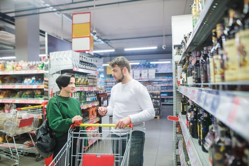 美好的夫妇在超级市场选择物品 一年轻人和一次女孩谈话在超级市场购物期间 免版税图库摄影