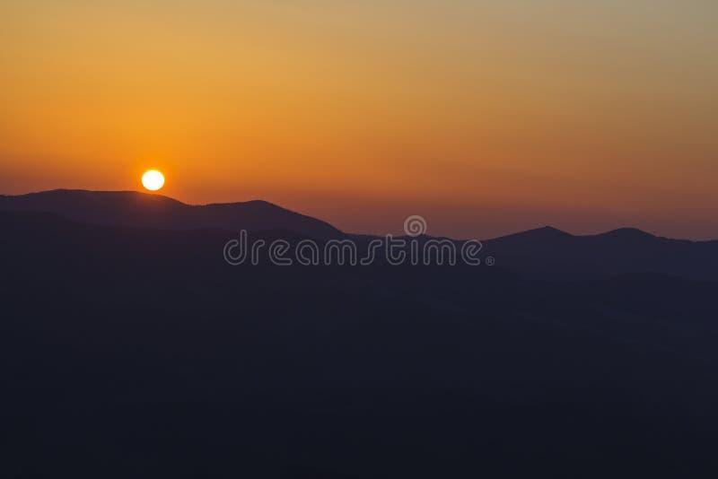 美好的山日落 大明亮的白色太阳宽全景视图在剧烈的橙色天空的在黑暗的山脉 库存照片