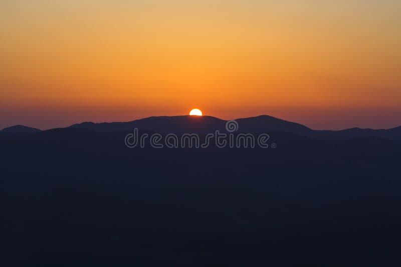 美好的山日落 大明亮的白色太阳宽全景视图在剧烈的橙色天空的在黑暗的山脉 免版税库存照片