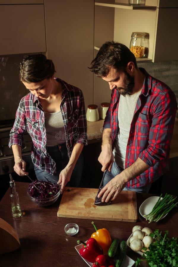 美好的年轻夫妇在厨房里在家,当烹调健康食品时 丈夫裁减圆白菜 妻子混合沙拉 场面从家庭生活 库存照片