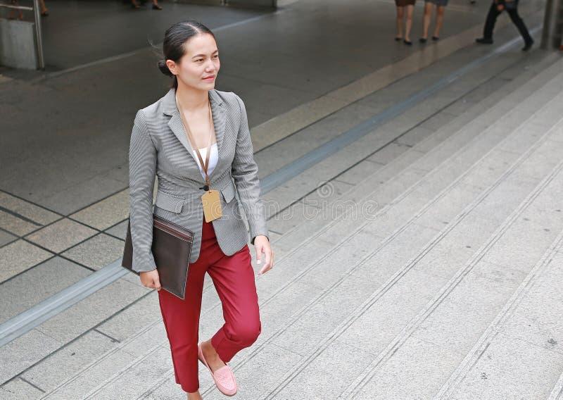 美好的年轻女商人走的外部 亚裔女实业家办公室工作者在街市商业区 库存照片