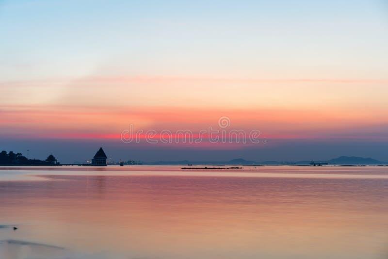 美好的海日落晚上和与剪影寺庙大厦和货船的红色天空 免版税库存图片