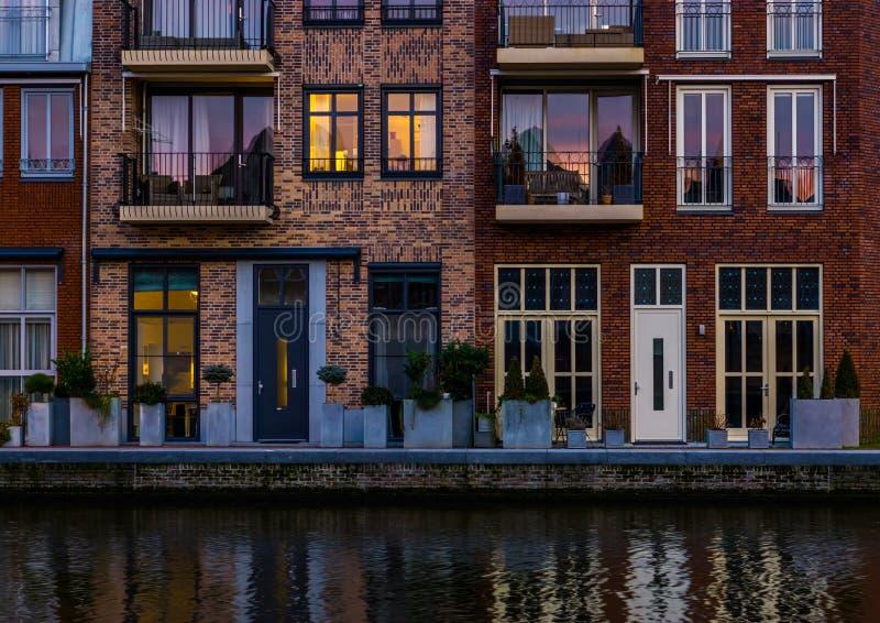 美好的现代荷兰城市建筑学在晚上,运河的有阳台的,莱茵河畔阿尔芬露台的房子, 库存照片