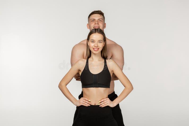 美好的运动的夫妇,在女孩后的赤裸上身的人身分 免版税库存照片