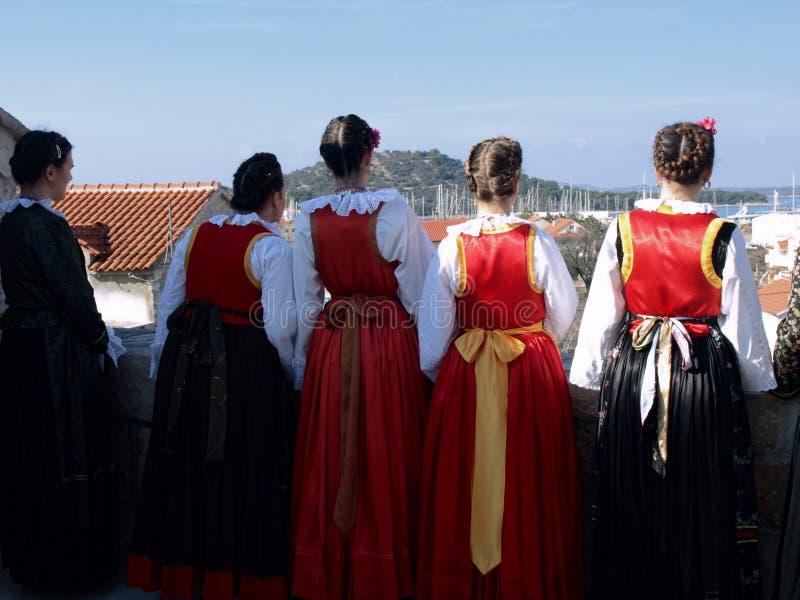 美妙,海岛,女孩,穿戴,民间,服装,房子,看法,船 库存图片
