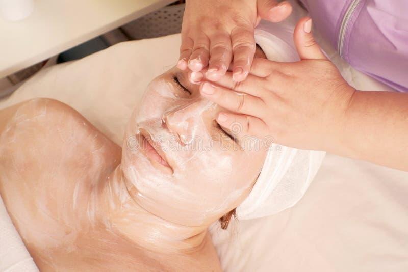 美容师应用在女性面孔的按摩奶油面具 成人亚裔妇女放松闭上她的在长沙发的眼睛在秀丽 免版税库存照片