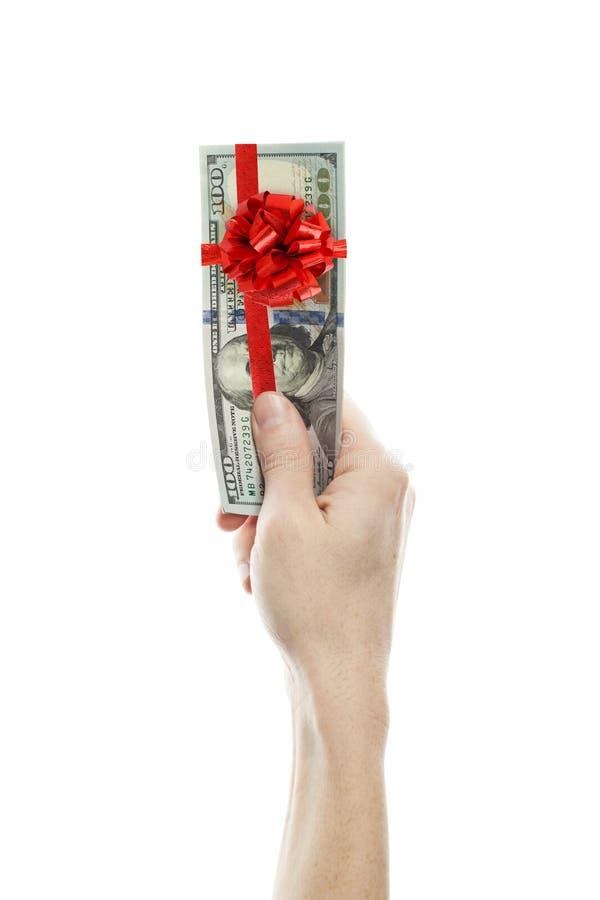 美元礼物赢利 与红色丝带的金钱现金和弓在白色背景隔绝的人手上 库存照片