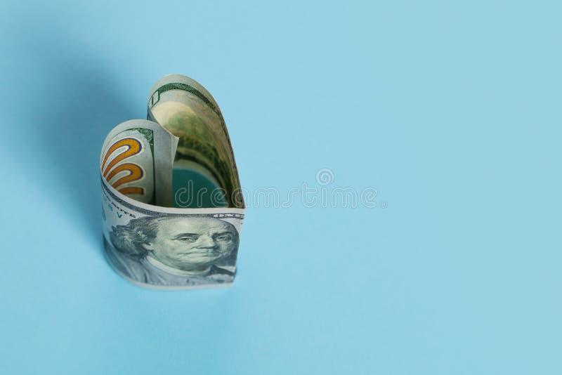美元现金金钱在蓝色背景、贷款和商业金钱投资赢利概念的钞票心形 免版税库存图片