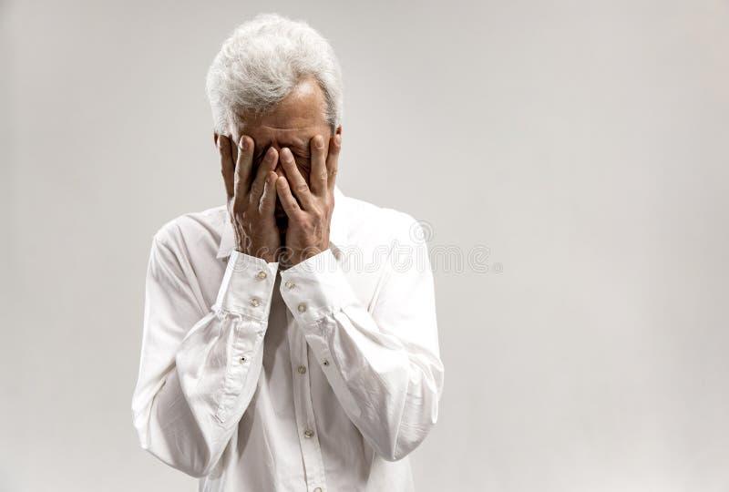 翻倒老人画象摩擦他的眼睛的,当哭泣时 库存图片