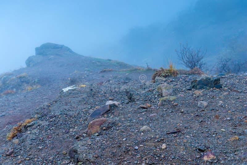 石头特写镜头,在山的路在厚实的秋天雾 免版税图库摄影
