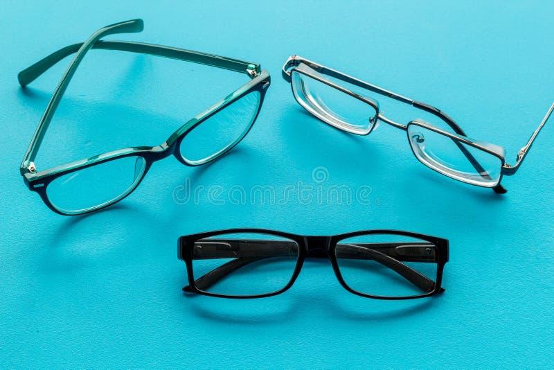 眼睛的辅助部件 与透明透镜的玻璃和在蓝色背景的不同的框架 免版税库存照片