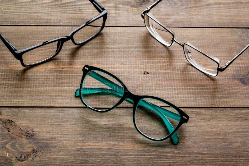眼睛的辅助部件 与透明透镜的玻璃和在黑暗的木背景的不同的框架 库存图片