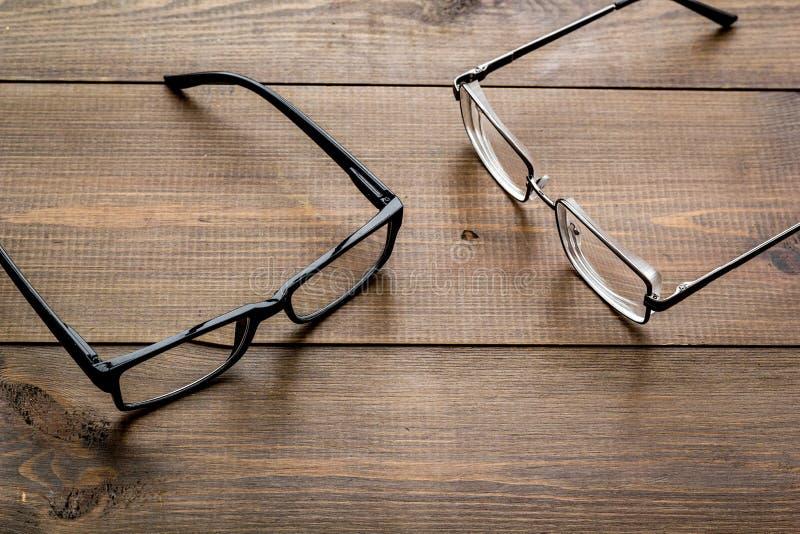 眼睛的辅助部件 与透明透镜的玻璃和在黑暗的木背景的不同的框架 免版税库存照片
