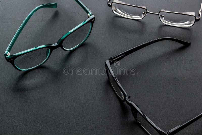 眼睛的辅助部件 与透明透镜的玻璃和在黑背景的不同的框架 免版税库存照片