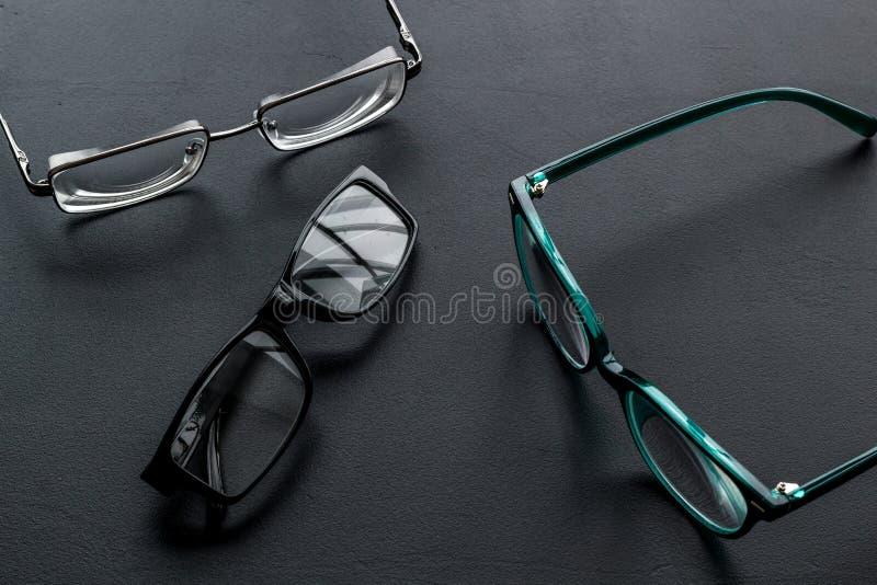 眼睛的辅助部件 与透明透镜的玻璃和在黑背景的不同的框架 库存图片