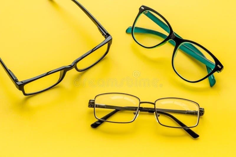 眼睛的辅助部件 与透明透镜的玻璃和在黄色背景的不同的框架 库存照片