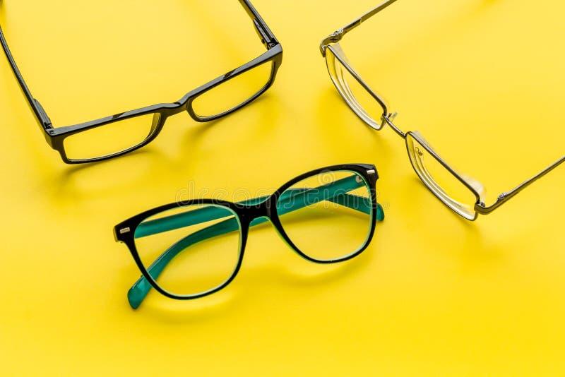 眼睛的辅助部件 与透明透镜的玻璃和在黄色背景的不同的框架 免版税库存照片