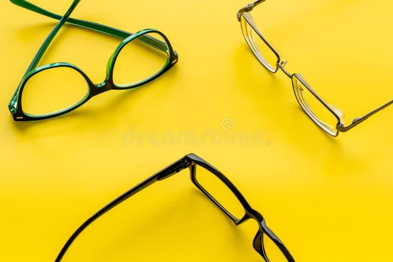 眼睛的辅助部件 与透明透镜的玻璃和在黄色背景的不同的框架 图库摄影