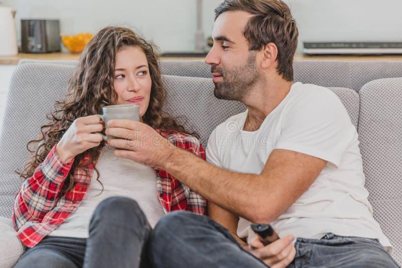 真的爱 快乐的浪漫夫妇坐在一舒适屋子和微笑的长沙发 库存照片