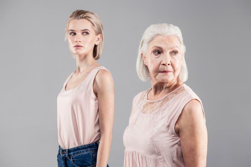 看一看的老灰发的妇女后边,当她的女儿时 免版税库存照片