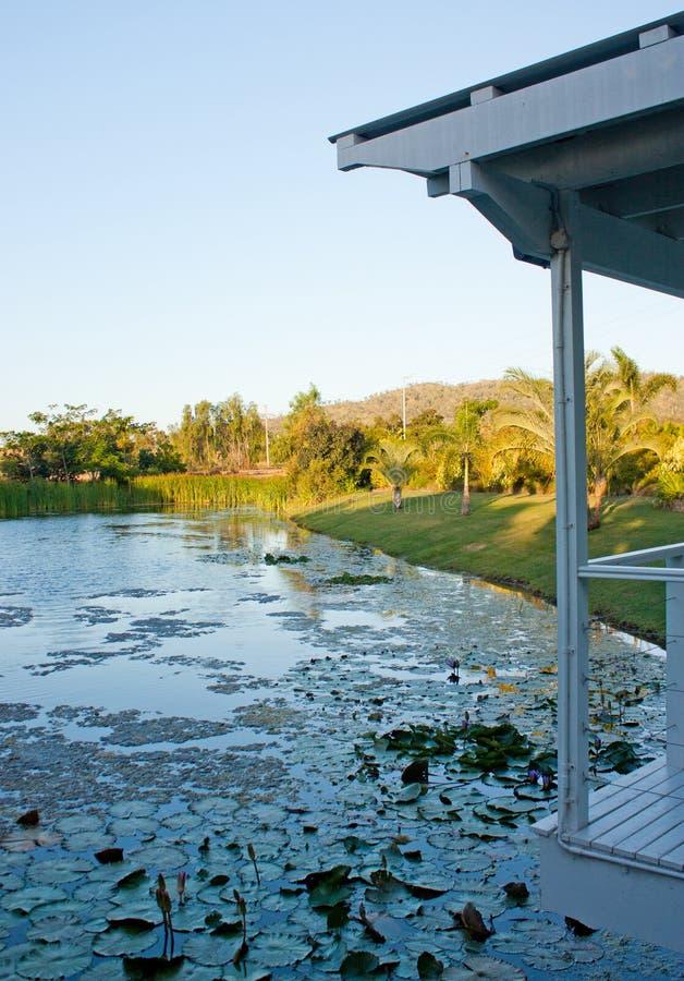 看从一个白色庭院房子/眺望台/树荫处的一个池塘在昆士兰,在日落期间的澳大利亚 库存图片