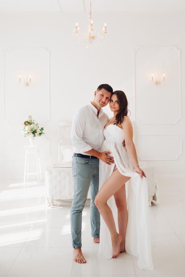 看从孕妇的旁边美丽的白色礼服的 库存照片