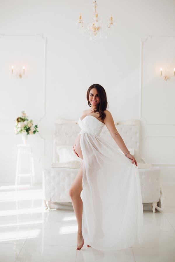 看从孕妇的旁边美丽的白色礼服的 免版税库存照片