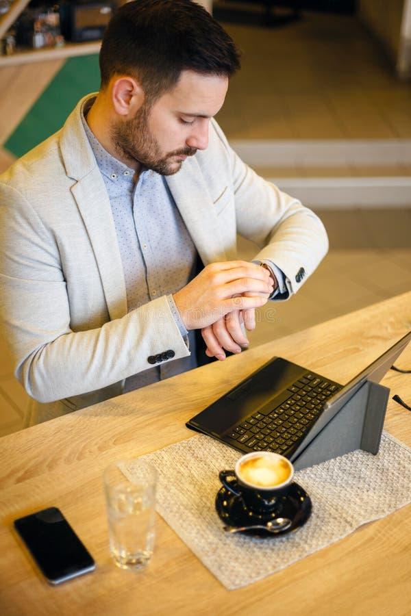 看他的手表的成功的年轻商人,运转在咖啡馆 库存照片