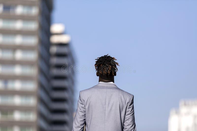 看反对天空蔚蓝的一非洲黑人年轻人的背面图在城市 免版税图库摄影