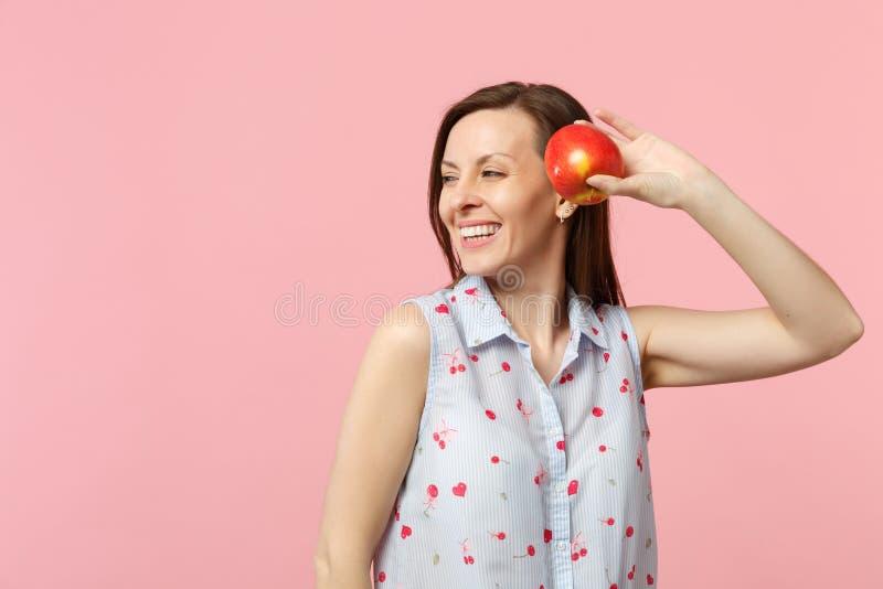 看夏天的衣裳的微笑的年轻女人在旁边拿着新鲜的成熟红色苹果果子被隔绝在桃红色柔和的淡色彩 免版税库存图片