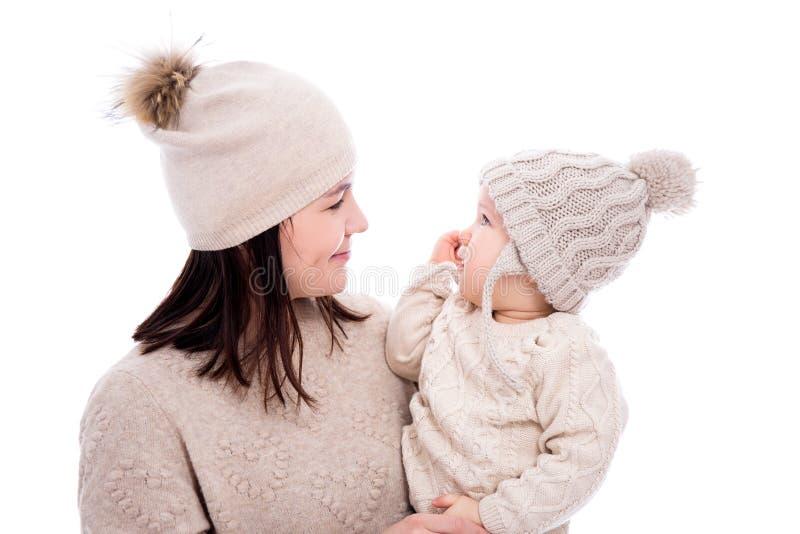 看彼此的冬季衣服的年轻母亲和可爱宝贝女儿在白色隔绝了 库存图片