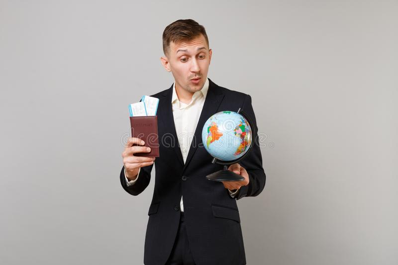 看在地球世界地球的黑衣服藏品护照登机牌票的好奇年轻商人被隔绝  免版税图库摄影