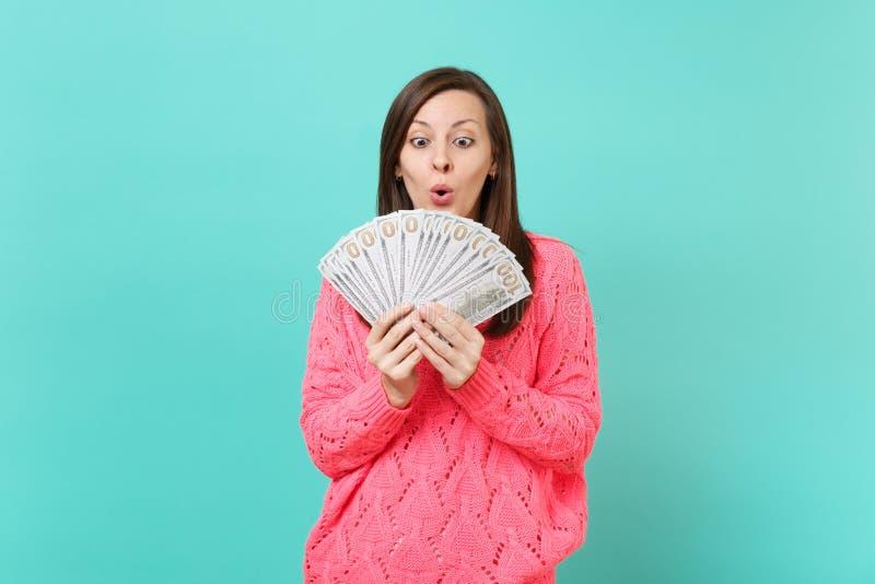 看在全部束美元钞票,现金金钱的被编织的桃红色毛线衣的震惊年轻女人在被隔绝的手上  免版税库存图片