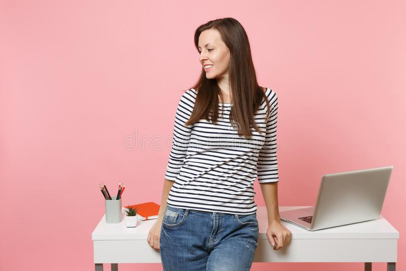 看在旁边工作和倾斜在有在粉红彩笔隔绝的个人计算机膝上型计算机的白色书桌上的便服的年轻俏丽的妇女 图库摄影