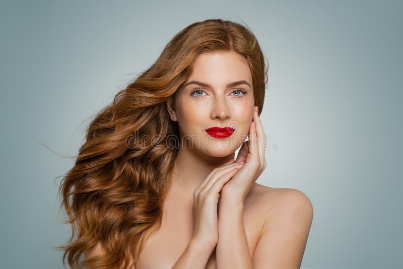 看在蓝色背景的时髦的可爱的年轻红头发人妇女照相机 免版税库存图片