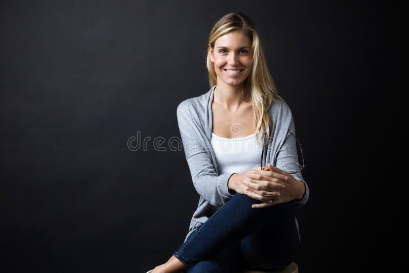 看在黑背景的美丽的年轻愉快的妇女照相机 免版税库存图片