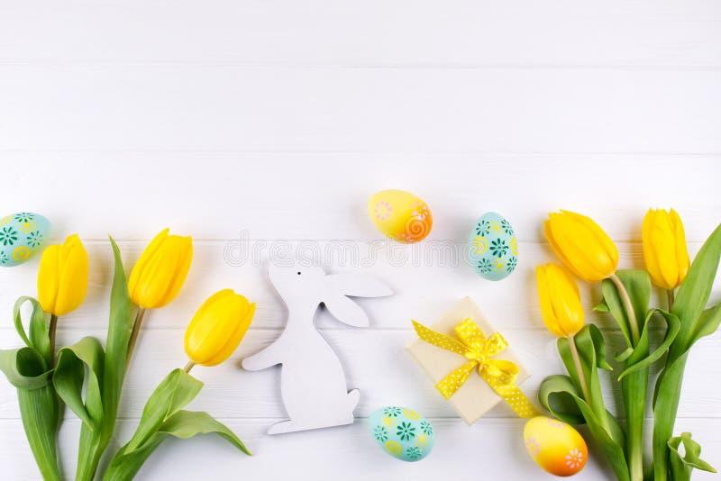 看板卡愉快的复活节 与黄色郁金香和复活节彩蛋的与拷贝空间的框架和兔宝宝在白色背景的文本的 库存照片
